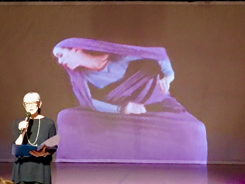 Janet Eilber, artistic director of the Graham Company, speaking to the audience about the 'Lamentation Variations,' with a film of Martha Graham's solo 'Lamentation' playing in the background.