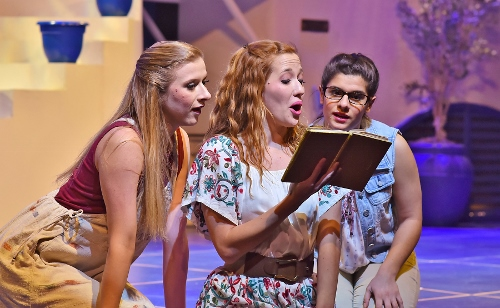 Sophie (Rachelle Rose Clark), center, reads the revealing stories in her mother's diary to her bridesmaids Lisa (Lauren Morgan), left, and Ali (Chloe Kounadis) in Beef & Boards Dinner Theatre's production of Mamma Mia! Now on stage, the Broadway mega-hit musical features the songs of the Swedish super group, ABBA, tells the story of a bride's search for her birth father on a Greek island paradise.
