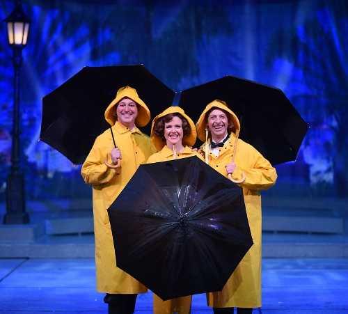 Trio with umbrellas: From left: Don Lockwood (Timothy Ford), Kathy Selden (Kimberly Doreen Burns), and Cosmo Brown (Buddy Reeder) are ready for Beef & Boards Dinner Theatre's production of 'Singin' in the Rain,' now on stage through May 26.