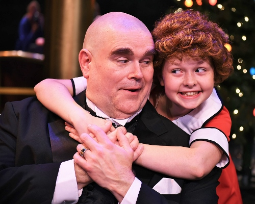 Annie and Daddy Warbucks: Annie (Claire Kauffman) puts her arms around Oliver Warbucks (Ty Stover) in Beef & Boards Dinner Theatre's production of Annie, now on stage through July 15.