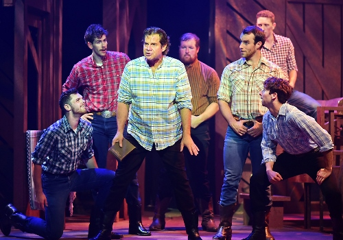 "Adam Pontipee (Tony Lawson), center, tells his brothers about a strategy for them to be with the women they love as he sings ""Sobbin' Women"" in Seven Brides for Seven Brothers, now on stage at Beef & Boards Dinner Theatre through Oct. 7. This rip-roaring stage version of the classic MGM film is bursting with energetic dance numbers and famous songs including ""Wonderful, Wonderful Day,"" ""Bless Your Beautiful Hide,"" and ""Goin' Courting."""