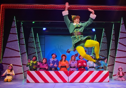 """Buddy (Dan Bob Higgins) kicks up his heels as he sings that he's """"Happy All The Time"""" in Christmastown at the North Pole in Beef & Boards Dinner Theatre's production of Elf, The Musical, now on stage through Dec. 31."""