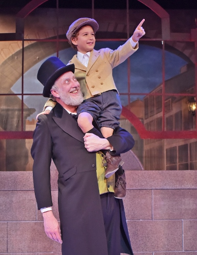 After finding redemption on Christmas Day, Ebenezer Scrooge (Jeff Stockberger) enjoys some time with Tiny Tim (Ashton Curry) in Beef & Boards Dinner Theatre's production of A Christmas Carol, on stage select dates through Dec. 21.