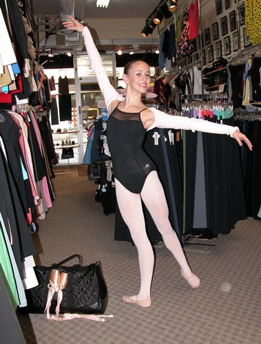 Pink shrug sweater by Harmonie. Black ABT Leotard by Capezio. Black quilted satin bag by Capezio. Modeled by Skylar Brandt. Available at <a href='http://www.onstagedancewear.com'>OnStageDancewear.com</a>.