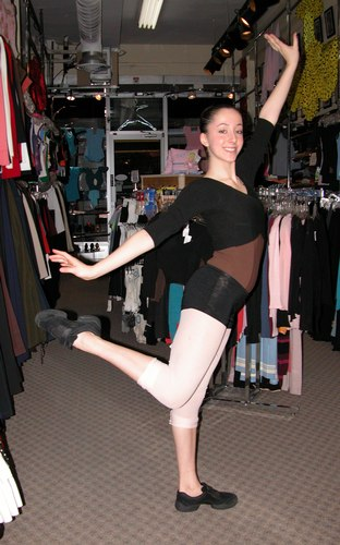 Emma is wearing a Black pullover from the Premiere Collection by Body Wrappers, style P930, $39.95; a Chocolate camisole leotard from the Premiere Collection by Body Wrappers, style P800, $44.99; and Black shorts from Harmonie, HW 304, L6, $28.95. Available at <a href='http://www.onstagedancewear.com'>OnStageDancewear.com</a>.