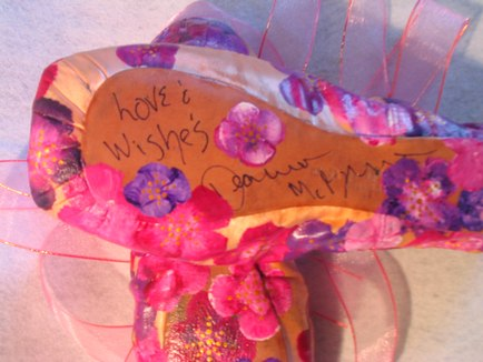 An example of a pair of pointe shoes (Autographed by former member of the New York City Ballet Diana McBrearty and, painted by Michelline Coonrod)
